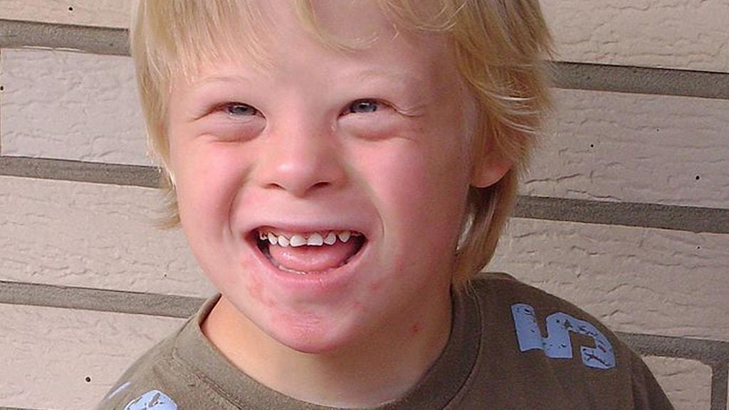 På fotot syns en ung kille med Downs syndrom. Han är blond och ler.