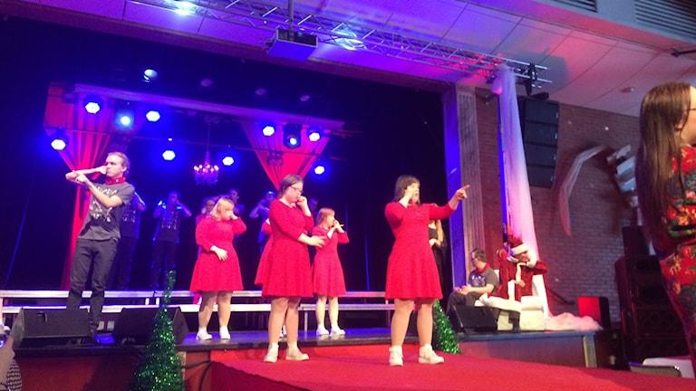 Fotot visar fyra tjejer i röda klänningar på scen som dansar och sjunger och en kille klädd i svart.