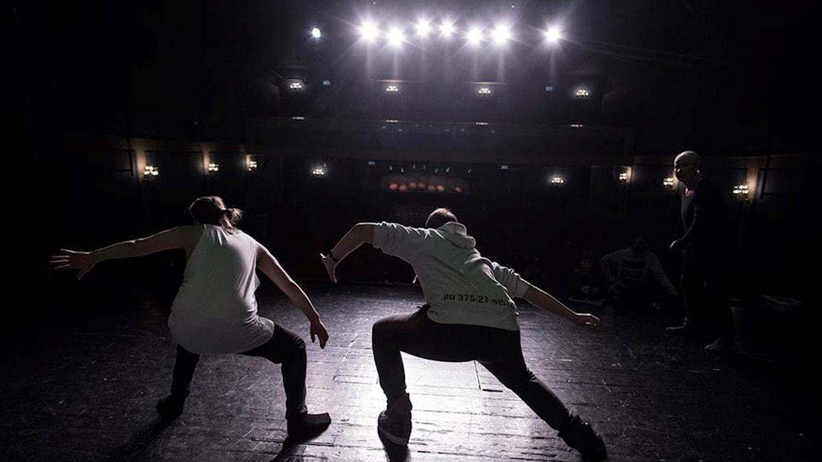 Två dansare gör rörelser på en scen. Starka strålkastare lyser på dem, men det är mörkt i resten av rummet.