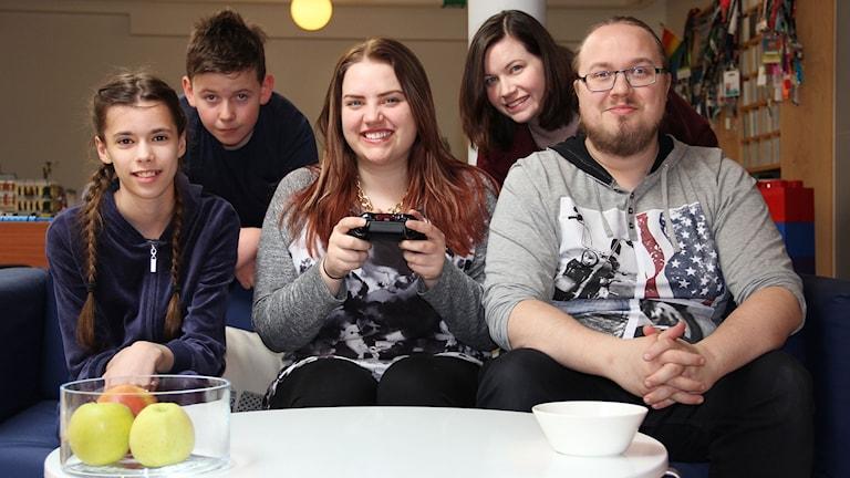Edith, Kim och David sitter i en soffa. Vilgot och Angelica står bakom.