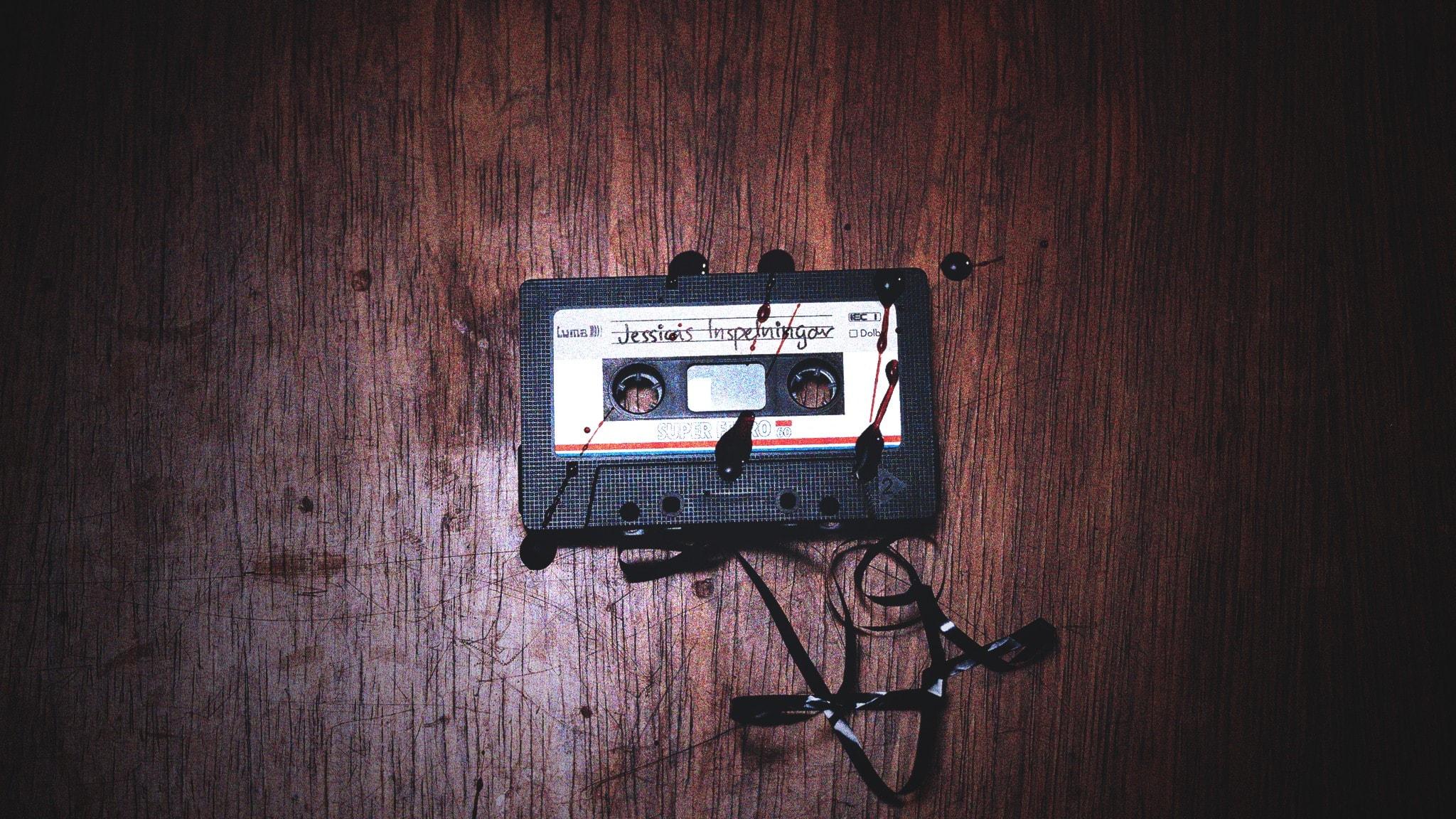 """Ett utdraget, blodbestänkt kassettband märkt """"Jessicas inspelningar"""" på ett repigt bord."""