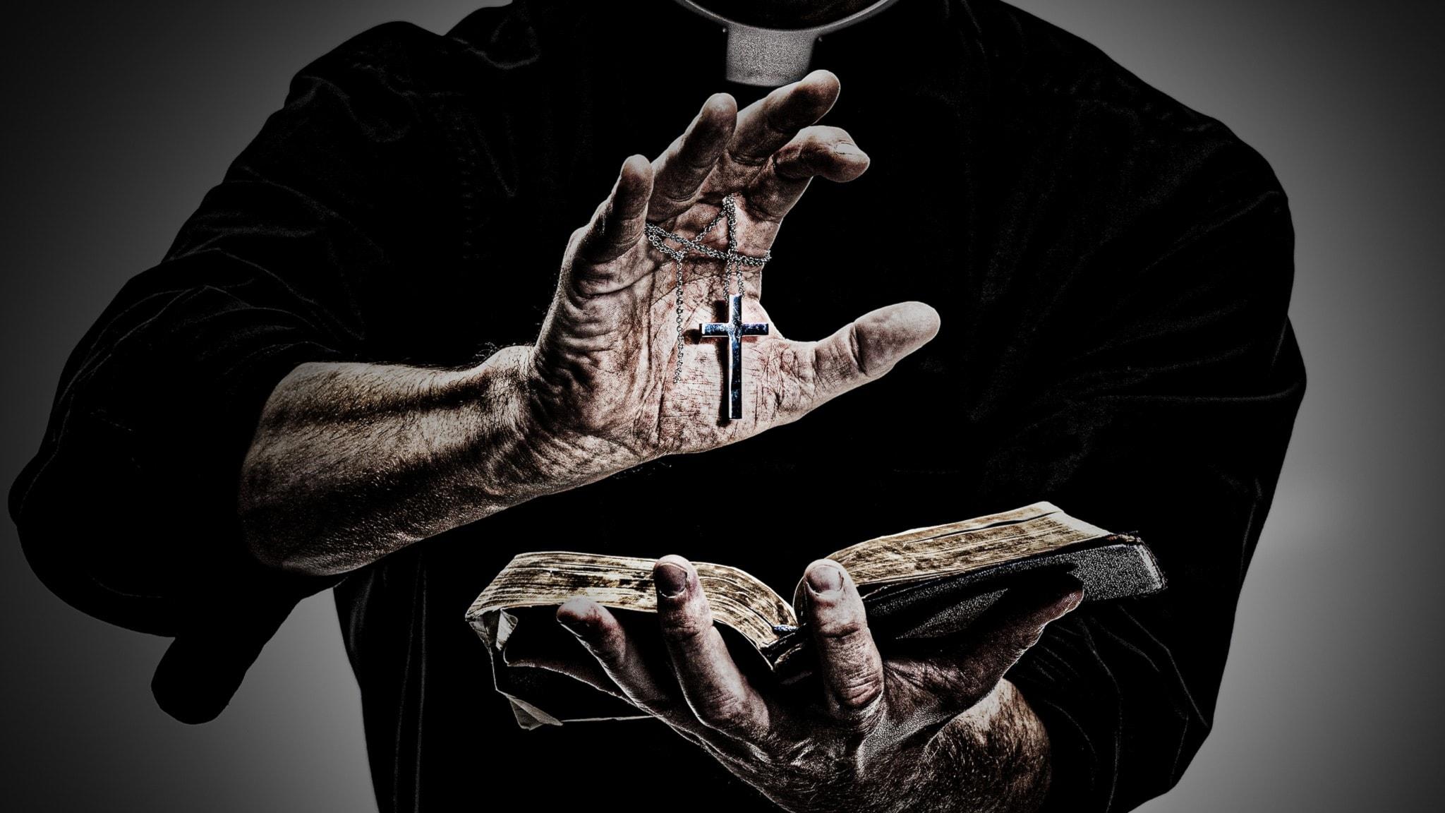 En präst håller i ett kors och en bok