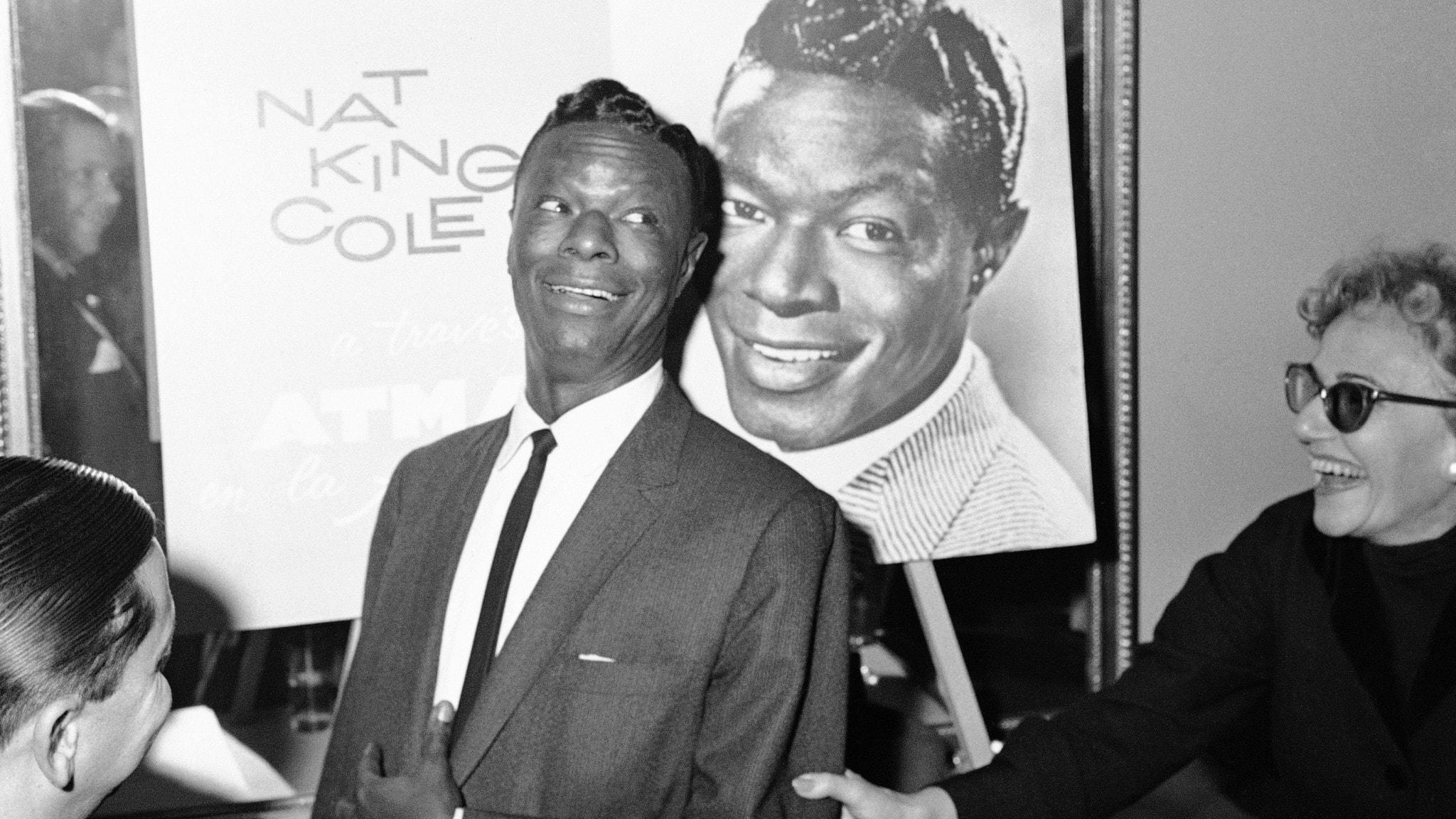 Nat King Cole framför en skylt med hans namn.