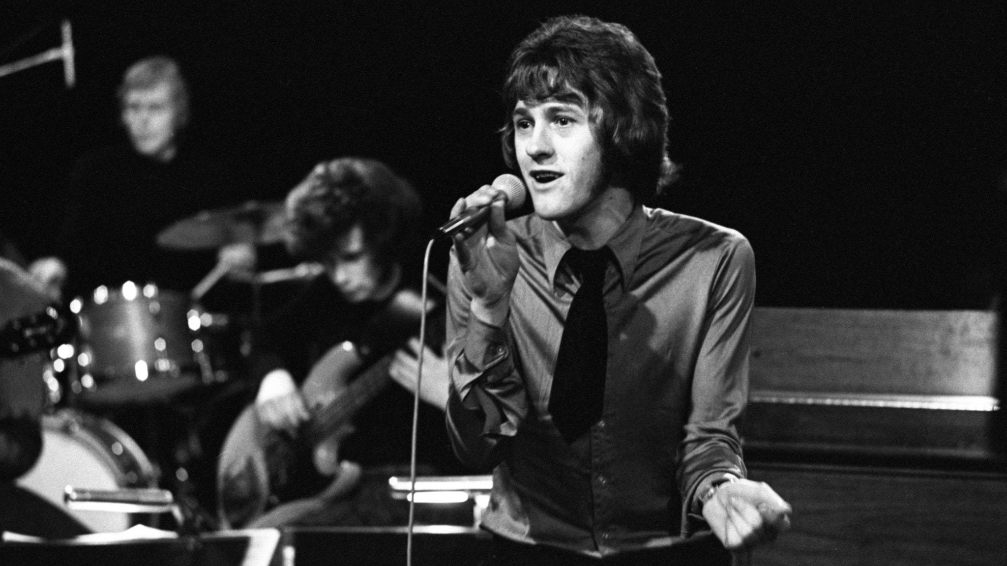 En ung Tommy Körberg står på scen med musiker bakom sig.  Han håller mikrofonen med ett mikrofonstativ nära mun med höger hand. Tommy bär skjorta och slips.