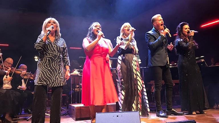 Fem artister på scenen , ståendes på rad, sjunger