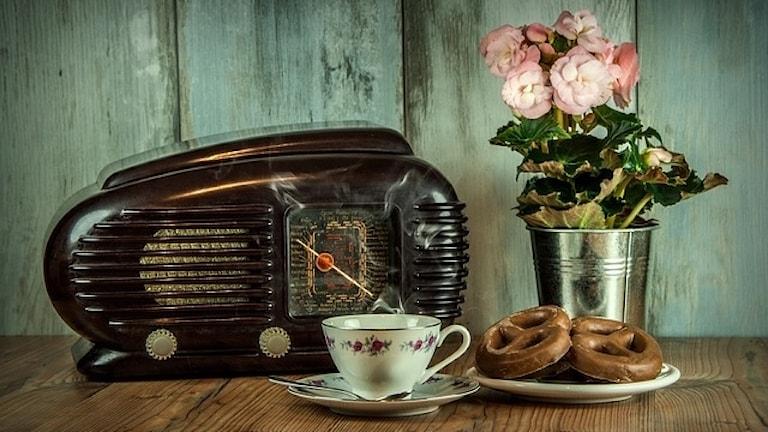 Radioapparat ståendes på bord tillsammans med kaffekopp, kringlor och blomma.