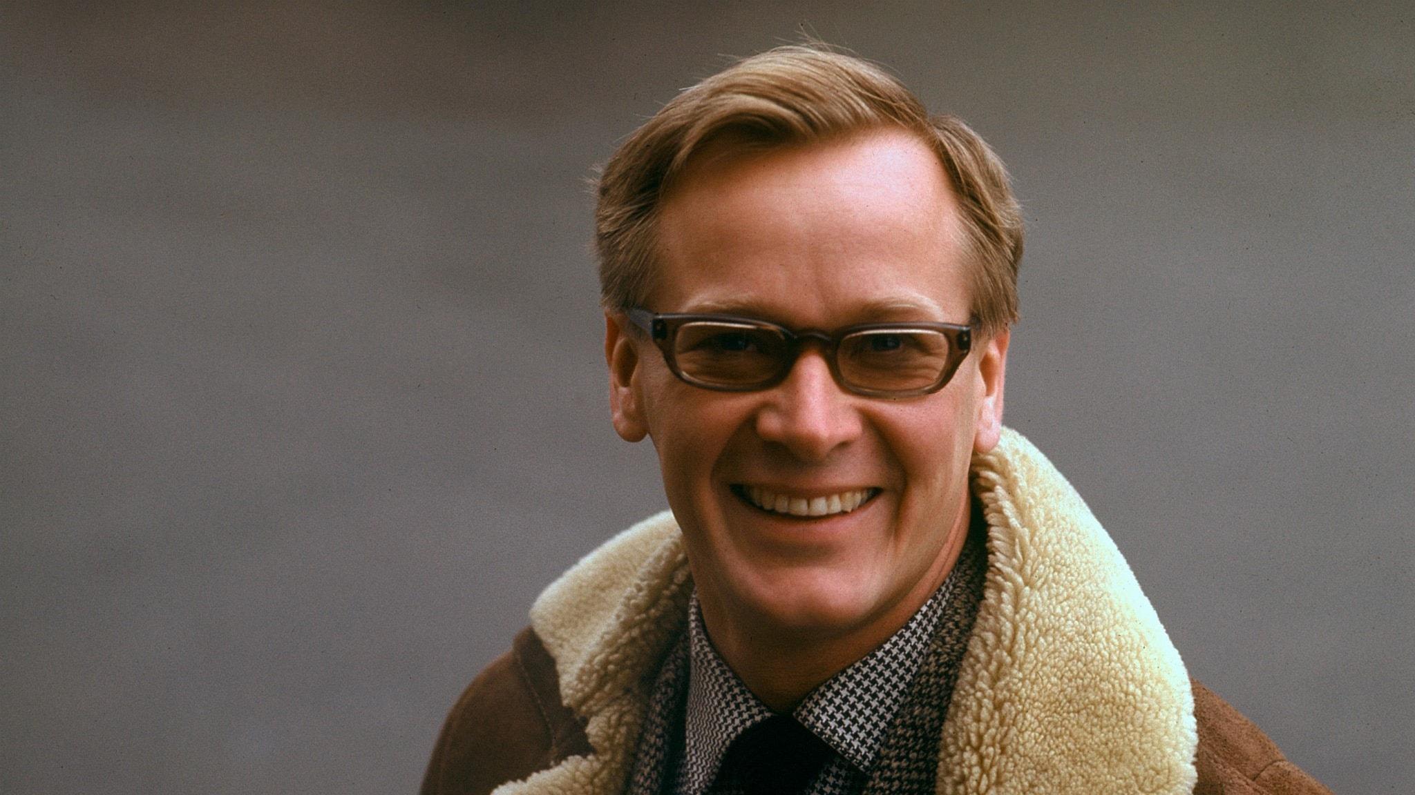 En ansiktsbild från 60-talet på Jan Malmsjö. Den är tagen utomhus kan man ana eftersom han har en brun jacka eller rock på sig med vit fårullsliknande krage. Jan bär glasögon.