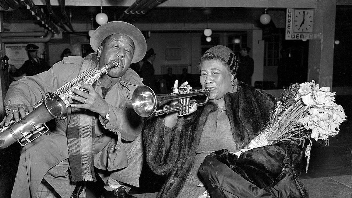 Jazz vocalist Ella Fitzgerald and trumpeter Roy Eldridge pose for photographers after arriving at the airport in Hamburg, West Germany on Feb. 15, 1954 for a tour of Germany with other top jazz figures. They were scheduled to appear before German audiences on promoter/producer Norman Grayz'