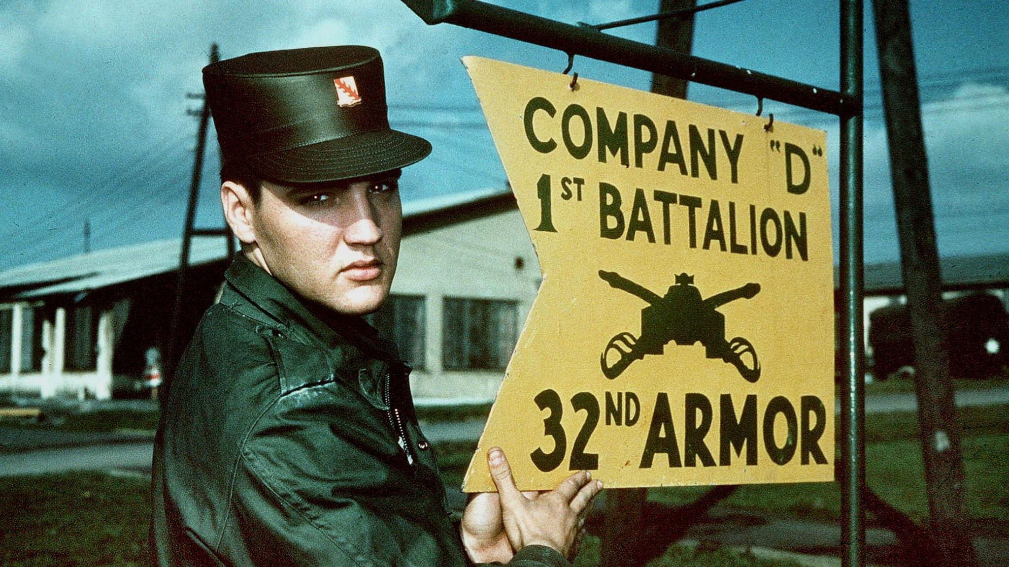 Elvis Presley är militärklädd och står vid en militärskylt