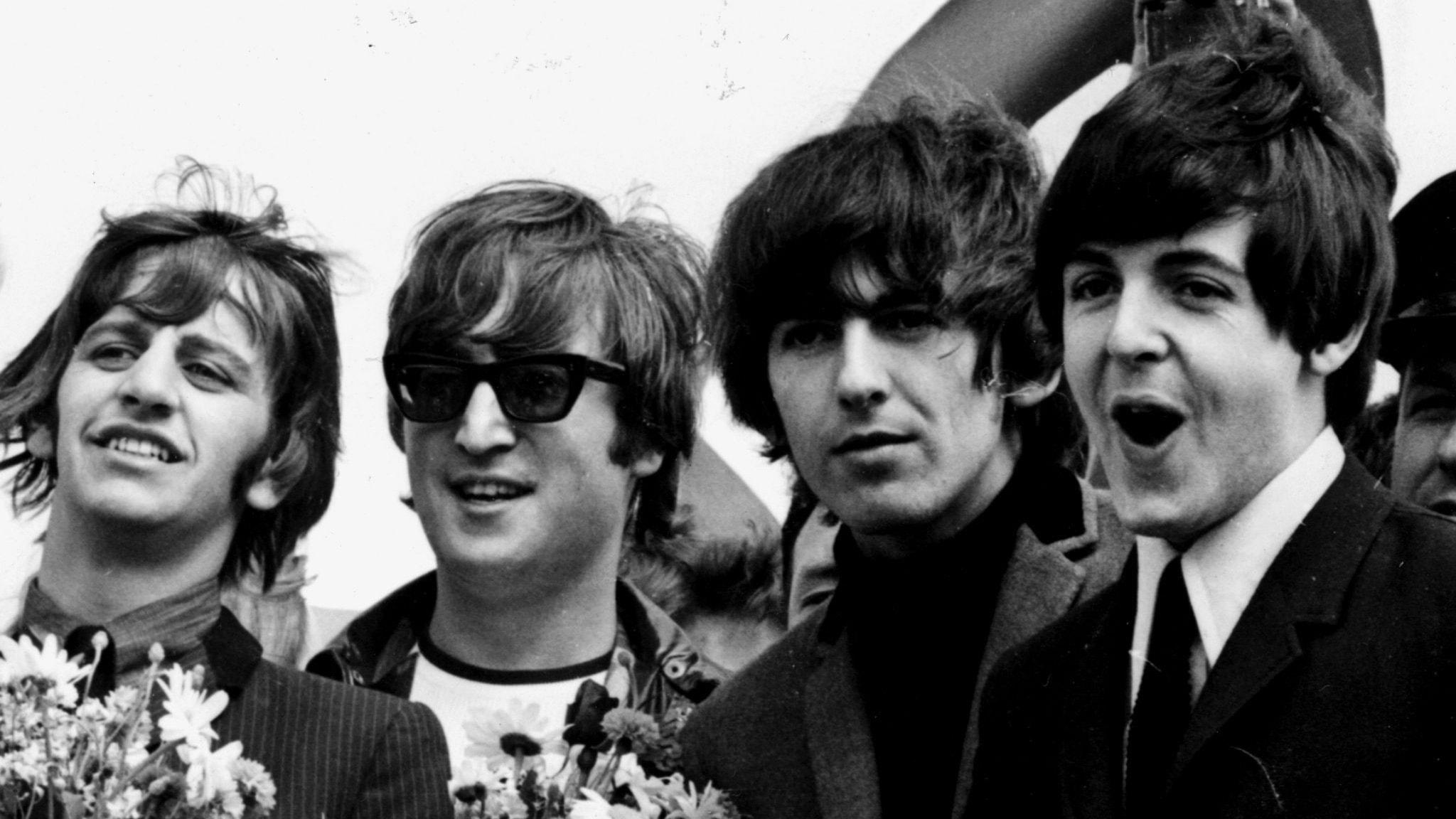 Svartvit bild på The Beatles som ler mot kameran