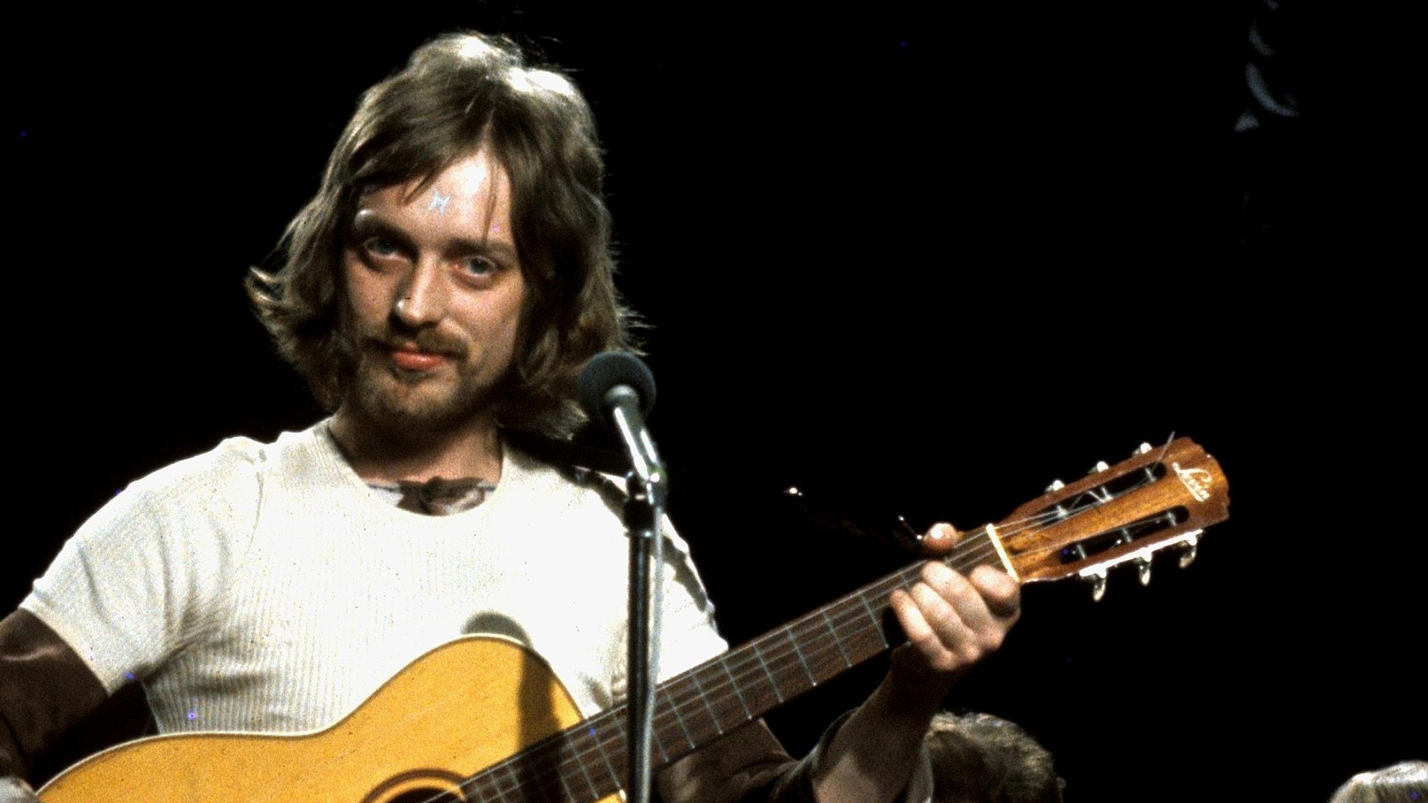 Pugh Rogefeldt står inför publik i TV 1972 och han bär en gitarr. Han ser allvarlig ut.