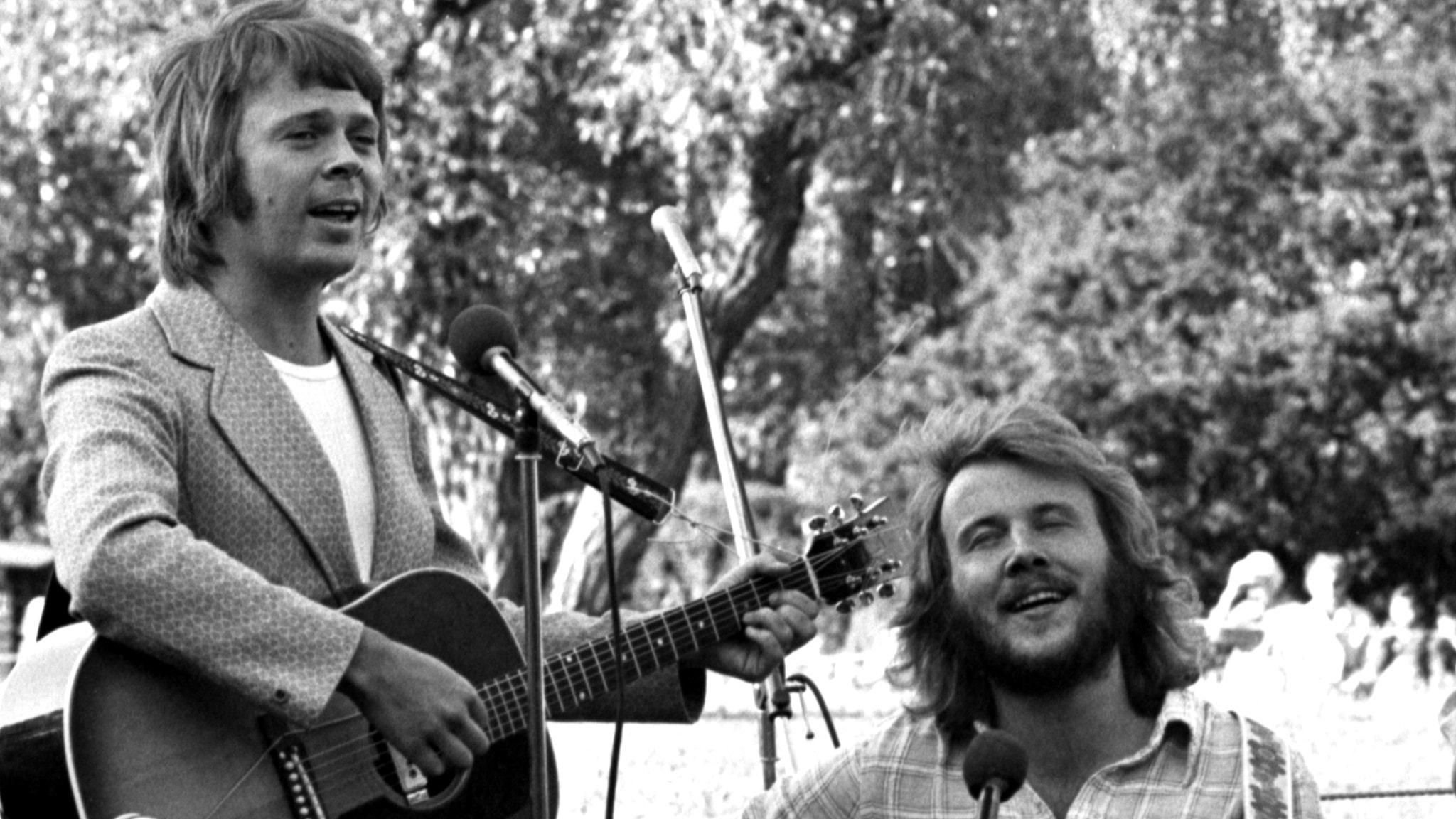 En svartvit bild när Björn Ulvaeus och Benny Andersson står inför publik. Björn håller i en gitarr och ser glad ut. Bilden är tagen sommaren 1971.