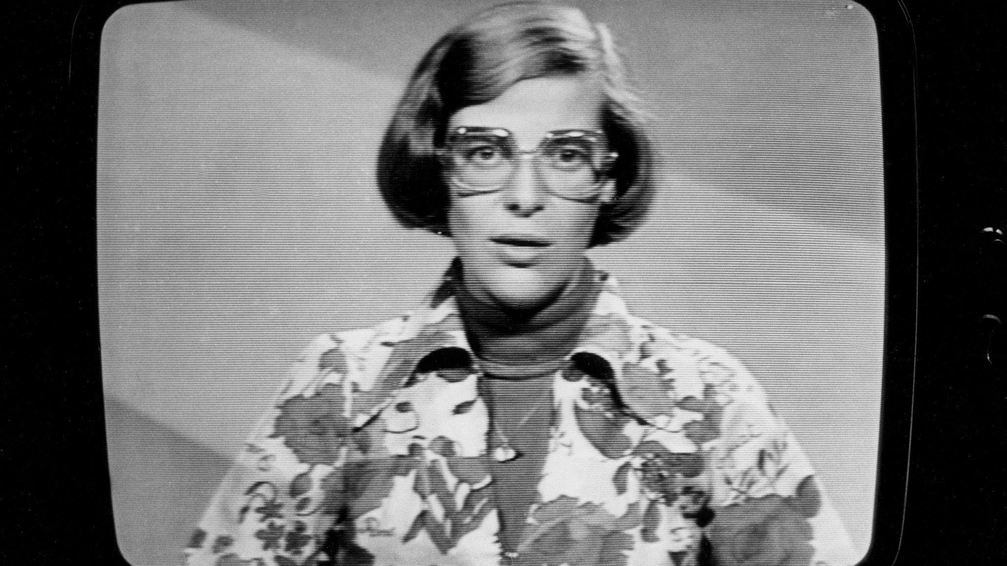En svartvit bild tagen på en bildrörs-TV när Åsa Bodén är synlig där. Hon ser allvarlig ut och bär glasögon.