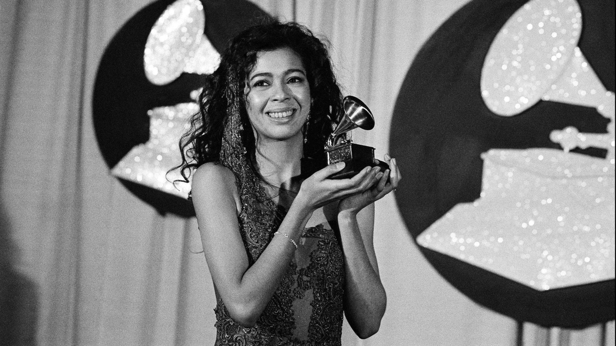 Irene Cara står och håller ett pris för sin musik. Priset består av en gammal trattgrammofon