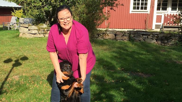 Ann-Sofie Stolpe med sin hund i trädgården