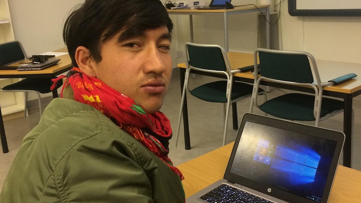Sarwar sitter i ett klassrum och arbetar på datorn