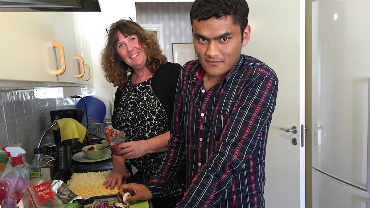 Pizzakväll. Mari och Alishah lagar mat tillsammans hemma i köket.