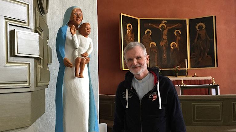 Träkonstnären och kyrkoherden Anders O Johansson visar en skulptur av en blond och blåögd Maria som tittar ut över besökarna i kyrkan.