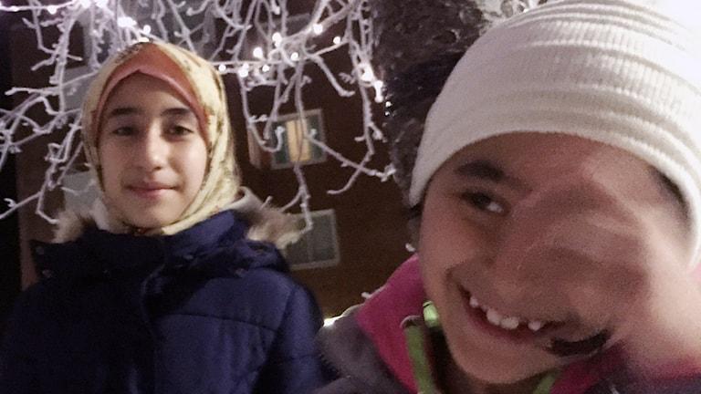 Asma Mousavi och lillasyster Fatema tycker att ljusen i de frostiga träden ger mysig stämning.