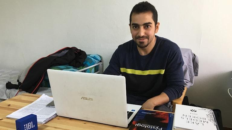 Sadeq sitter vid ett bord med sin dator och de många medicinska böcker han har lånat inför kunskapsprovet.