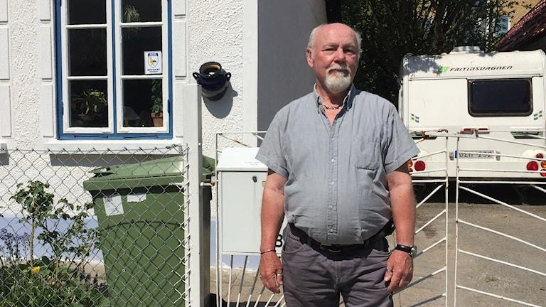 Leif Jönsson står framför sitt hus en solig sommardag.