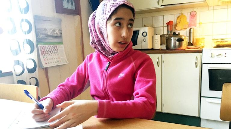 Asma Mousavi skriver upp receptet på lunchsoppan till P4 Norrbottens reporter.