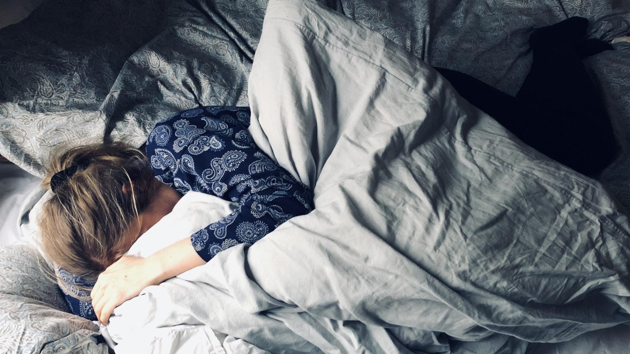 kvinna ligger i en obäddad säng med ansiktet dolt i täcket.
