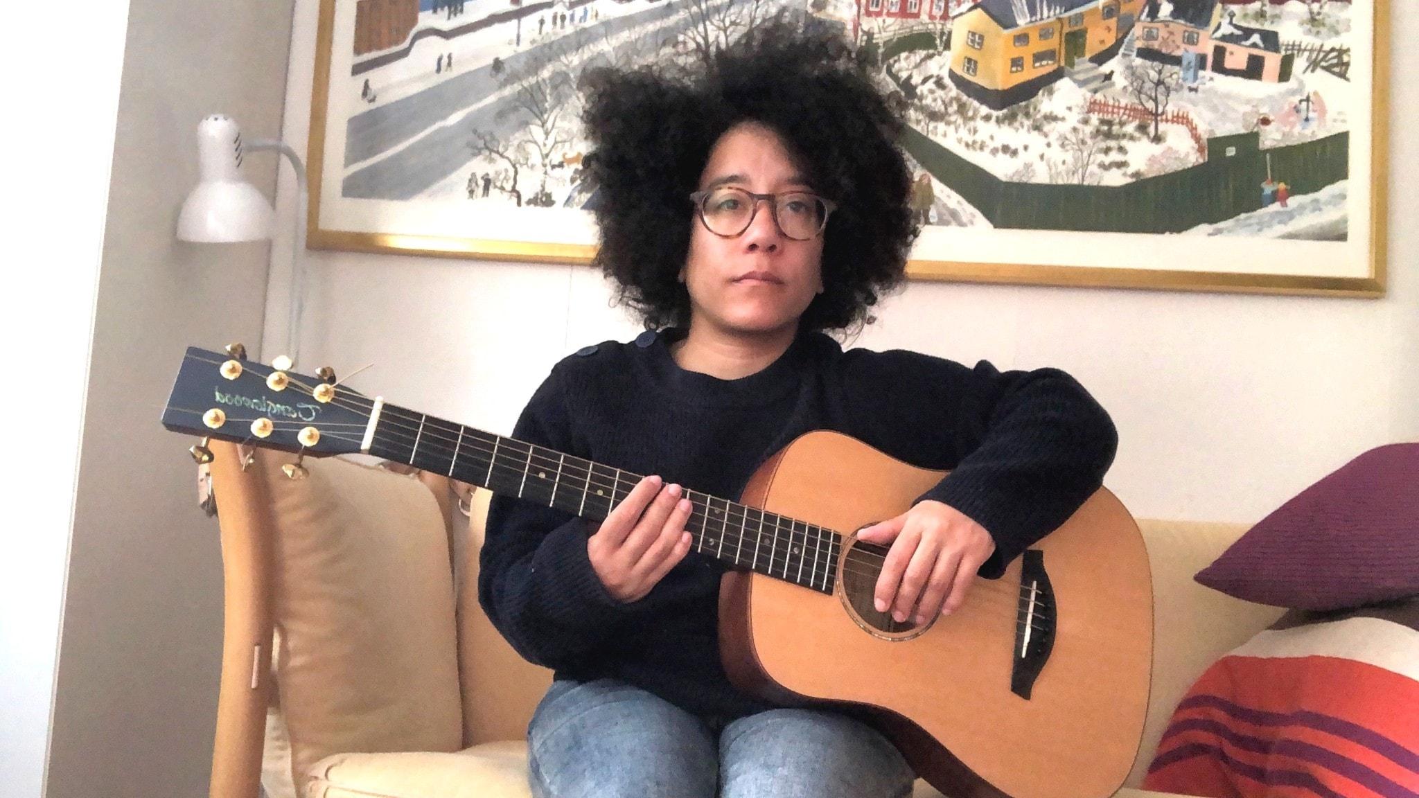 Catrine Lundell sitter i en soffa med en gitarr, allvarlig min.