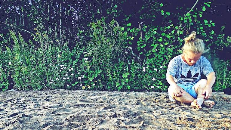 Man sittandes på strand