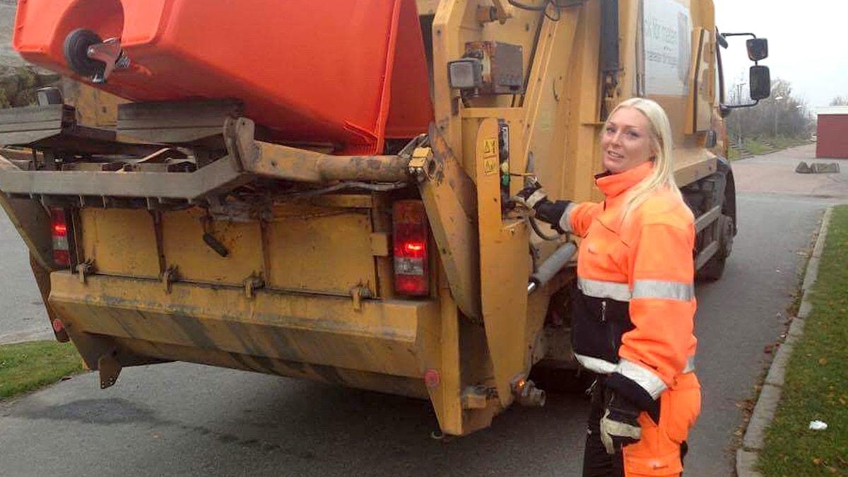 kvinna tömmer soptunna i lastbil