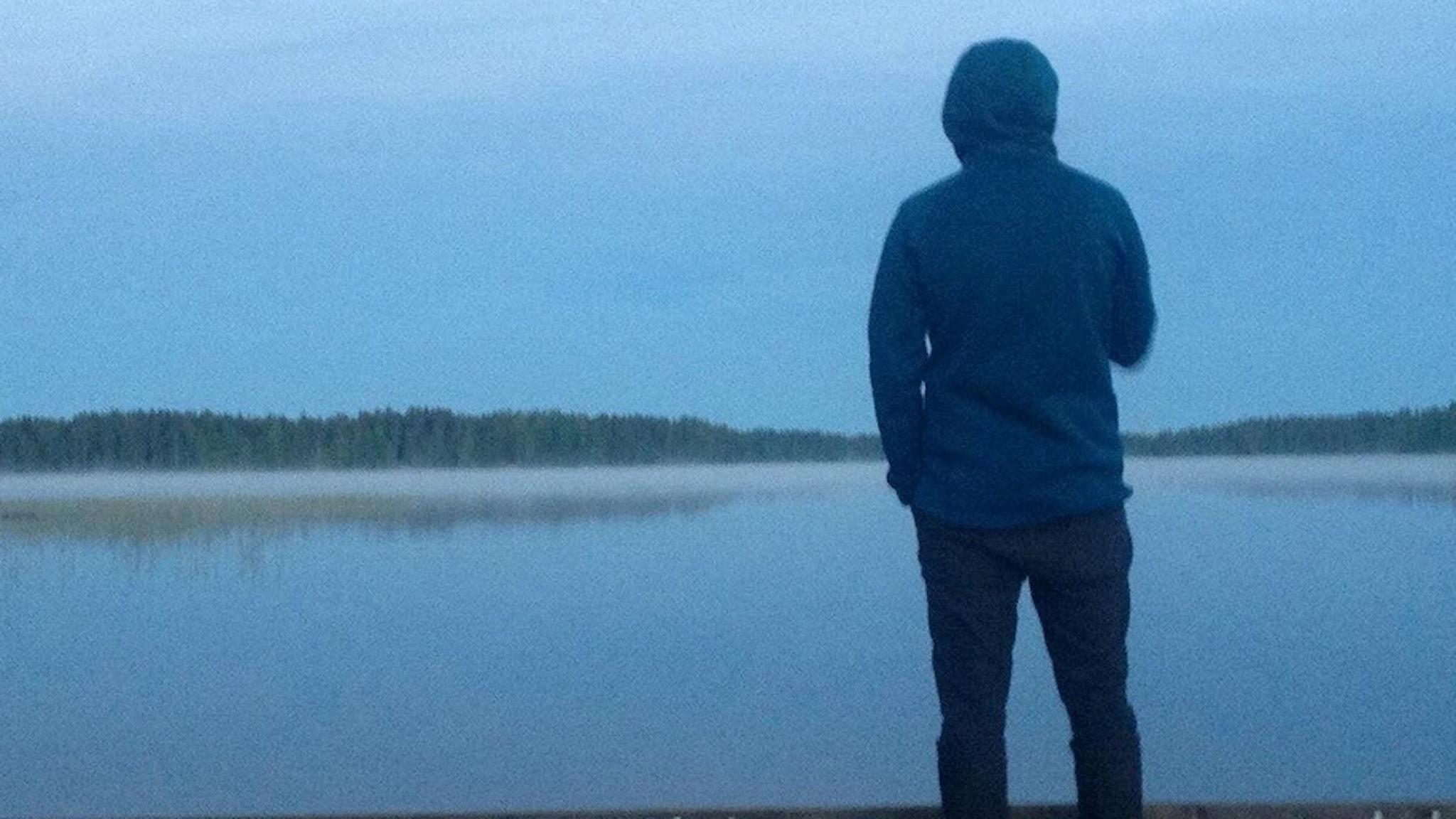 Josef står och blickar ut över en sjö.