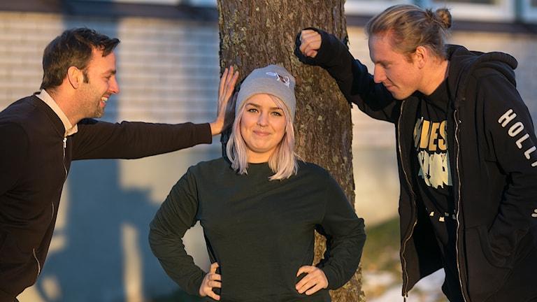 Man, kvinna och man framför ett träd