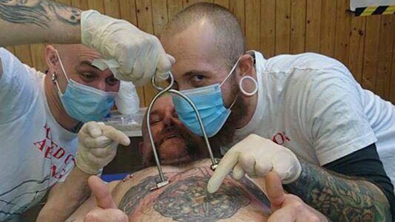Två killar sätter in en krok i en annan killes bröst, de håller på med body suspension.