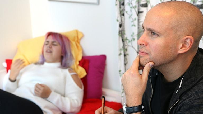 Kvinna sittande på säng och man sittande på stol