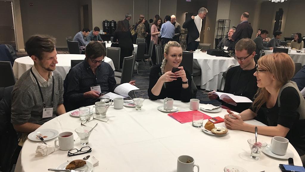 Två kvinnor och tre män pratar runt ett bord