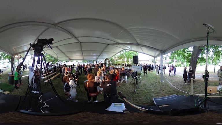 En utsmetad 360-bild från ett tält fyllt med kameror och människor.