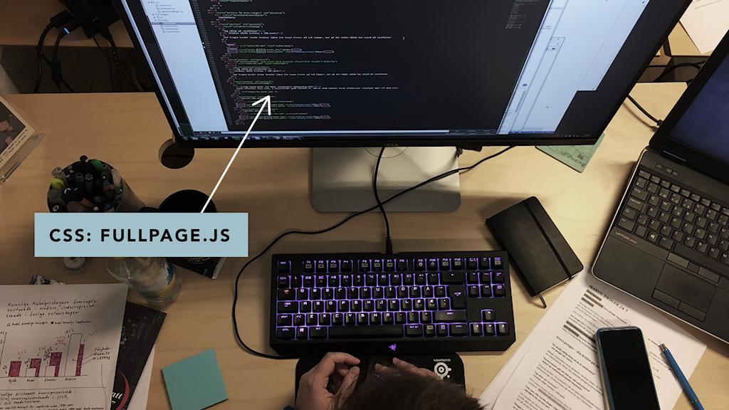 En stor datorskärm visar CSS-kod vid ett skrivbord. En pil och en skylt visar texten CSS: Fullpage.js.