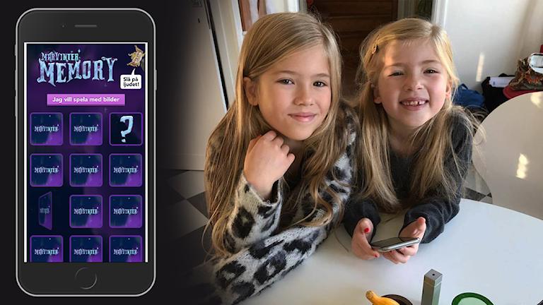 En mobilskärm visar memoryspel och bredvid står två små tjejer och ler in i kameran med en mobil i handen.