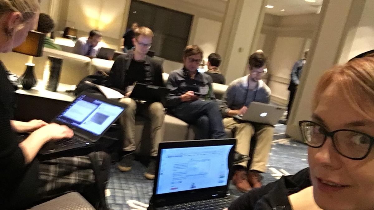 Tre män och två kvinnor med datorer