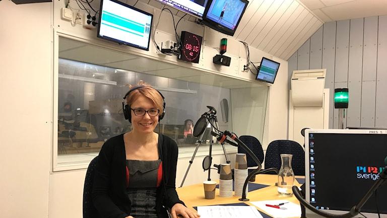 kvinna i en radiostudio, klädd i svart topp, hörlurar, glasögon.
