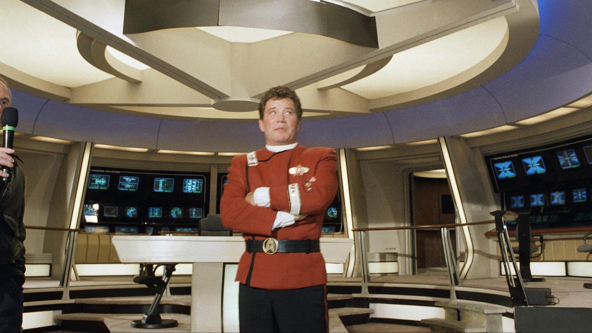 Bild på William Shatner iklädd sin Star Trek uniform stående på rymdskeppet Enterprises brygga