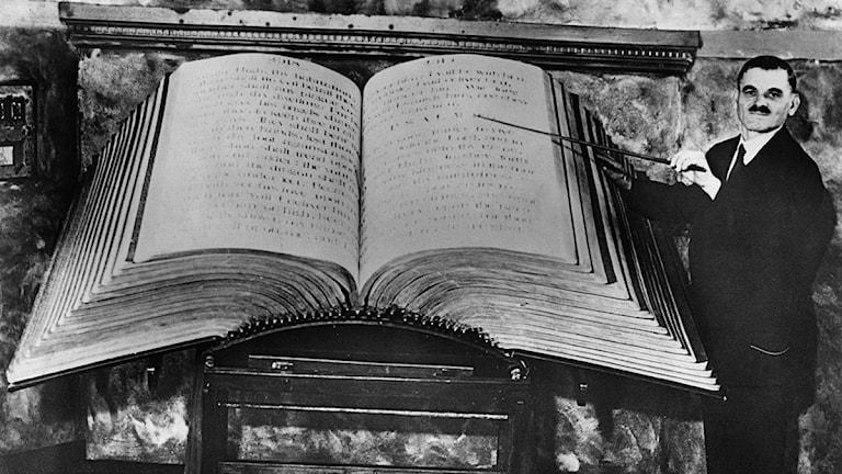 En jättestor bok och en man som står bredvid. Foto: SVT Bild