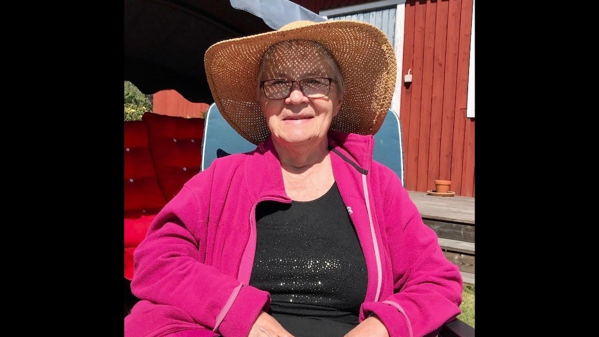 Kuvassa nainen istuu ulkona aurinkoisessa säässä, hattu päässä.