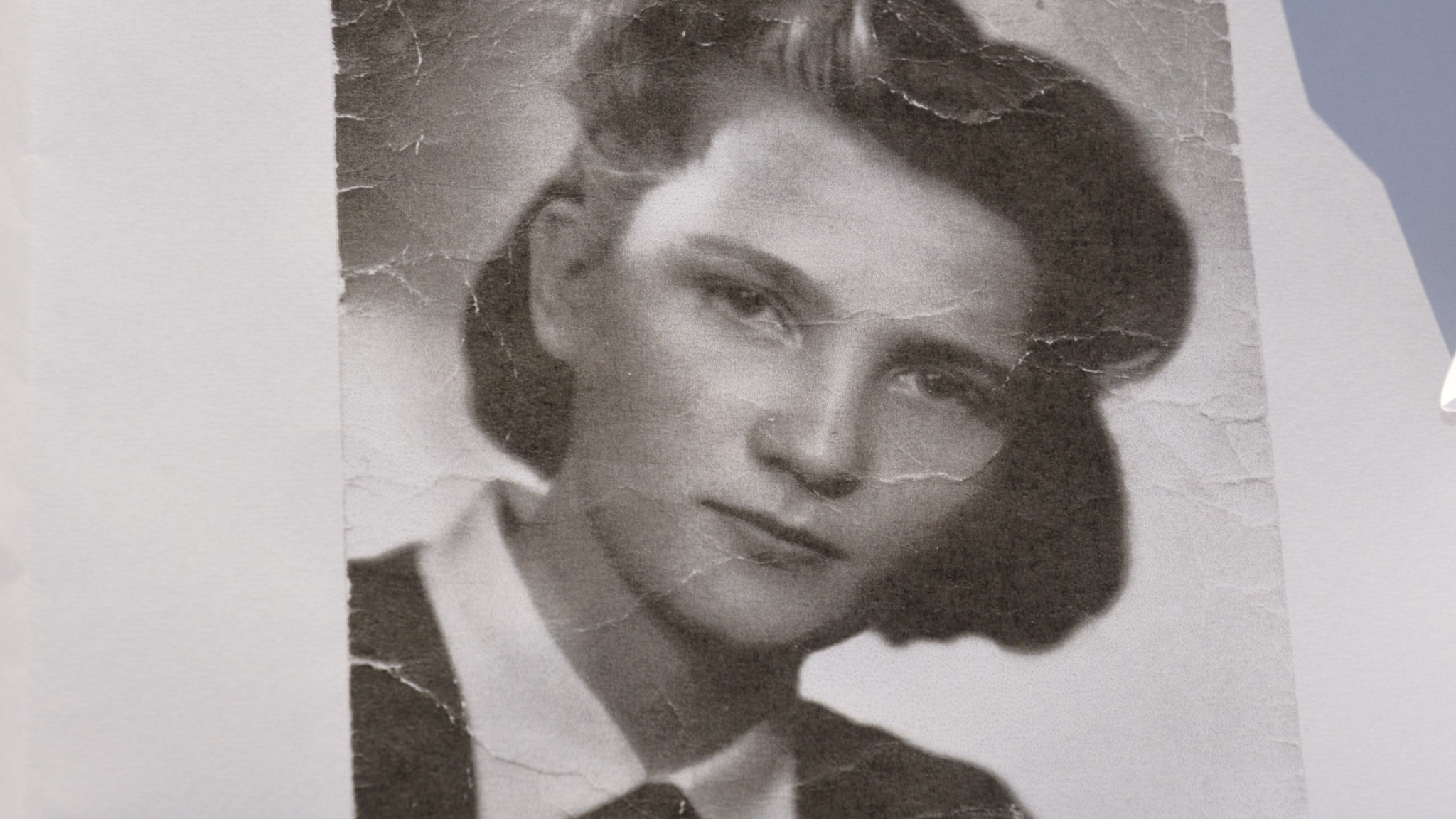 Kuva mustavalkoisesta valokuvasta jossa nuori nainen katsoo kameraan.