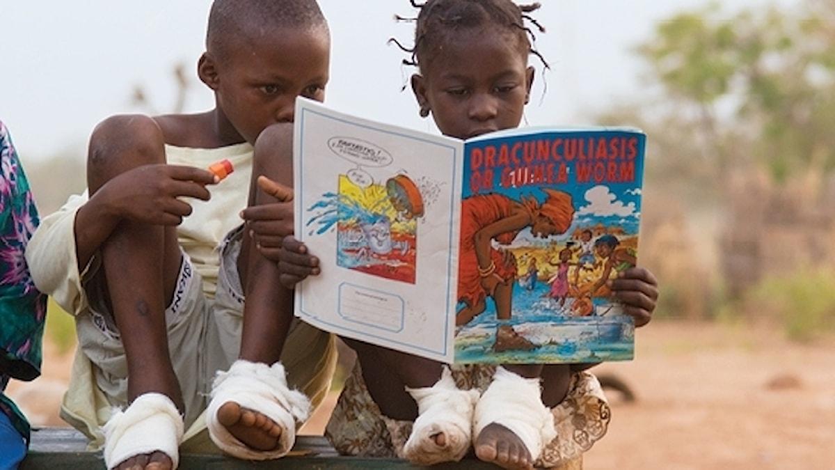 Bild på två barn som läser en serietidning med information om guineamask