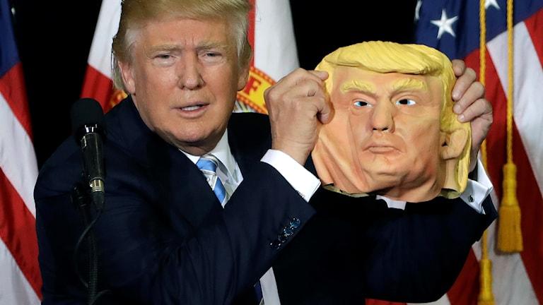 Donald Trump med en mask föreställande sig själv.