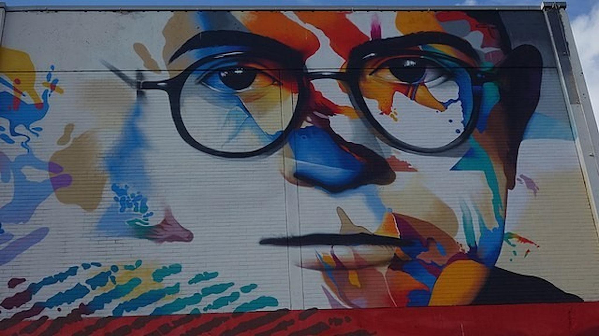 Muralmålning av ett glasögonprytt ansikte med färgglada mönster på en gatuvägg.