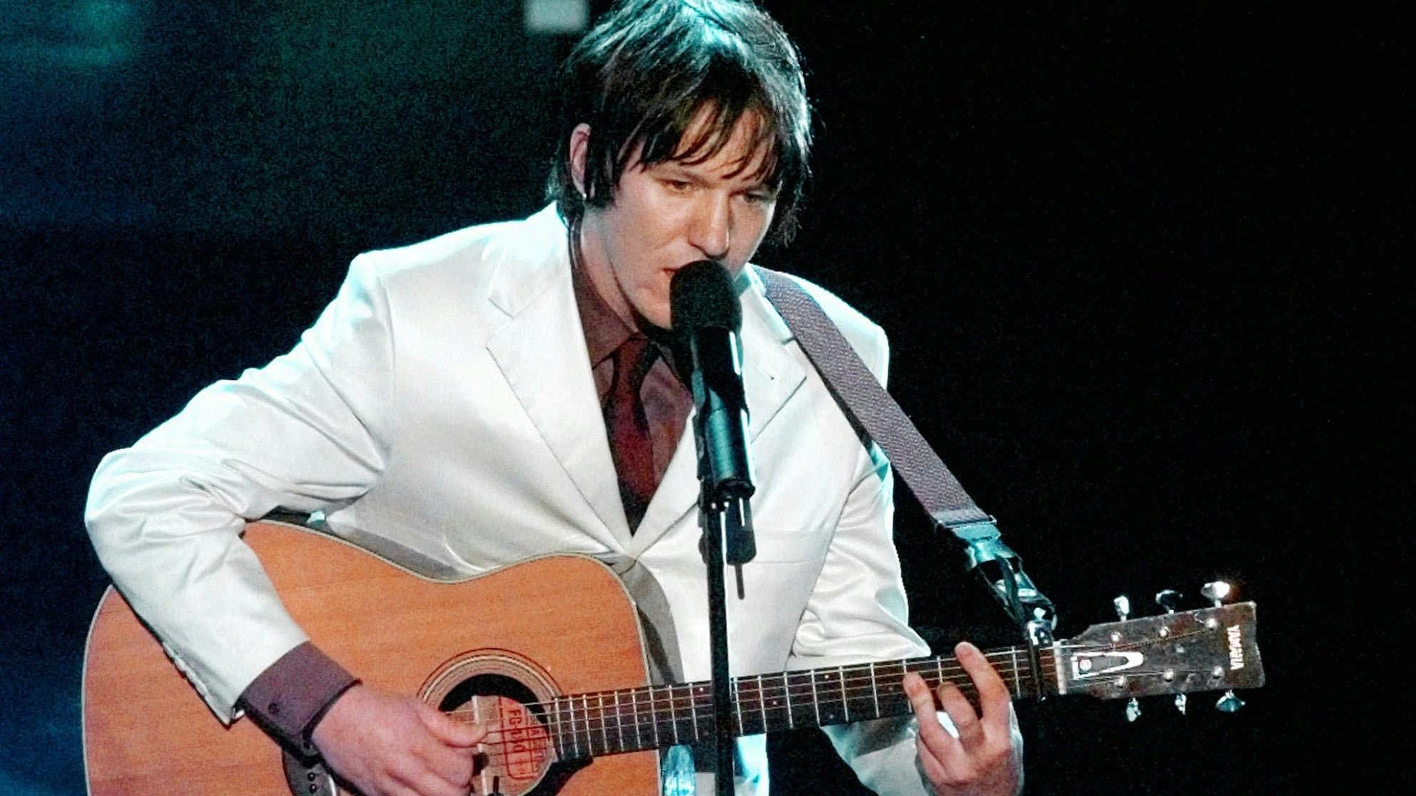 Man i vit kostym står på scen med gitarr i handen.