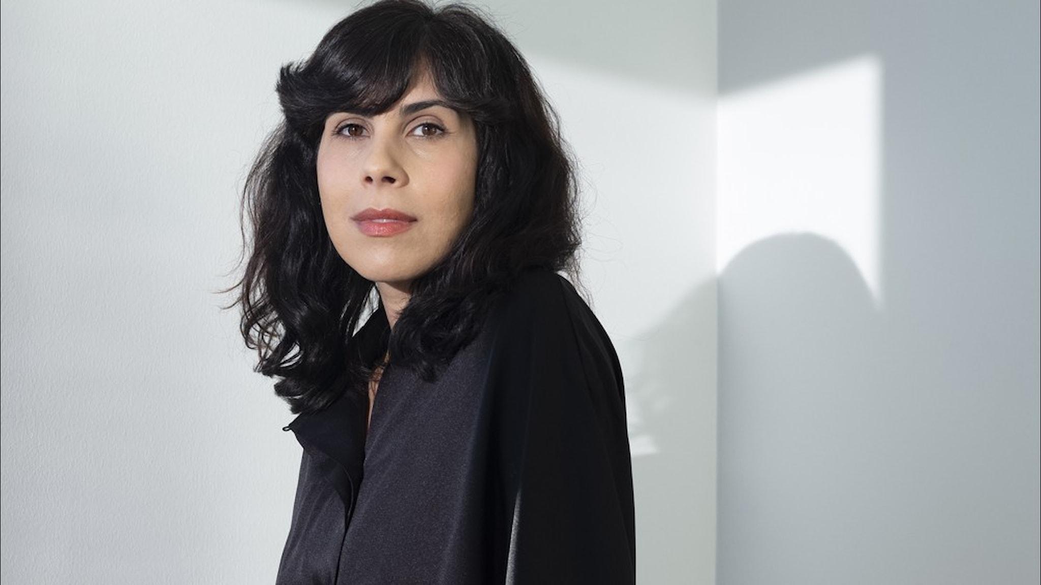 Författaren Elnaz Baghlanian klädd i svart mot vit bakgrund.
