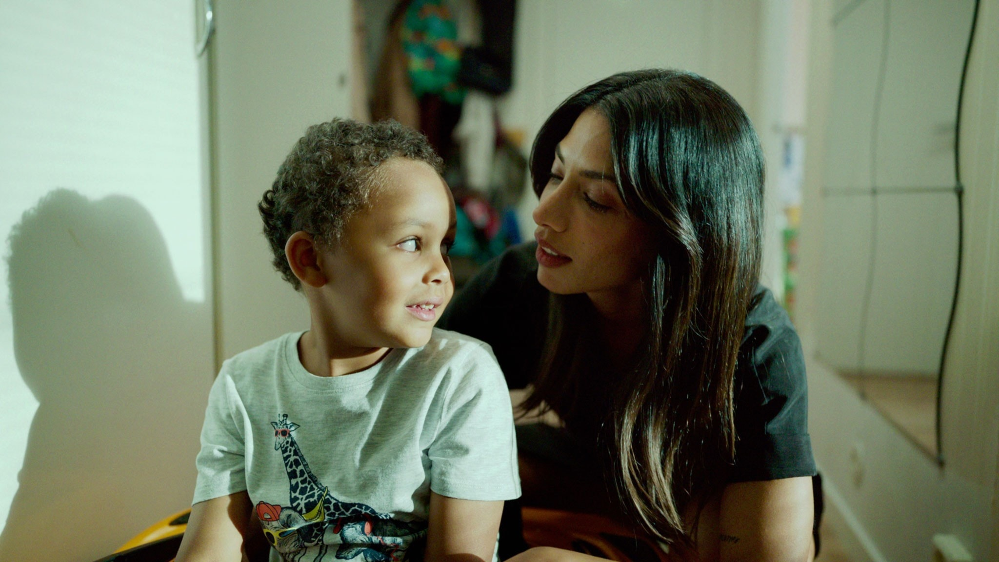 En mamma pratar med sin lille son cirka fyra år gammal klädd i mönstrad T-shirt.